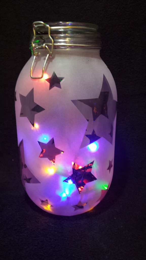 Multi coloured LED lights illuminating a large preserving jar with a reverse etched star pattern