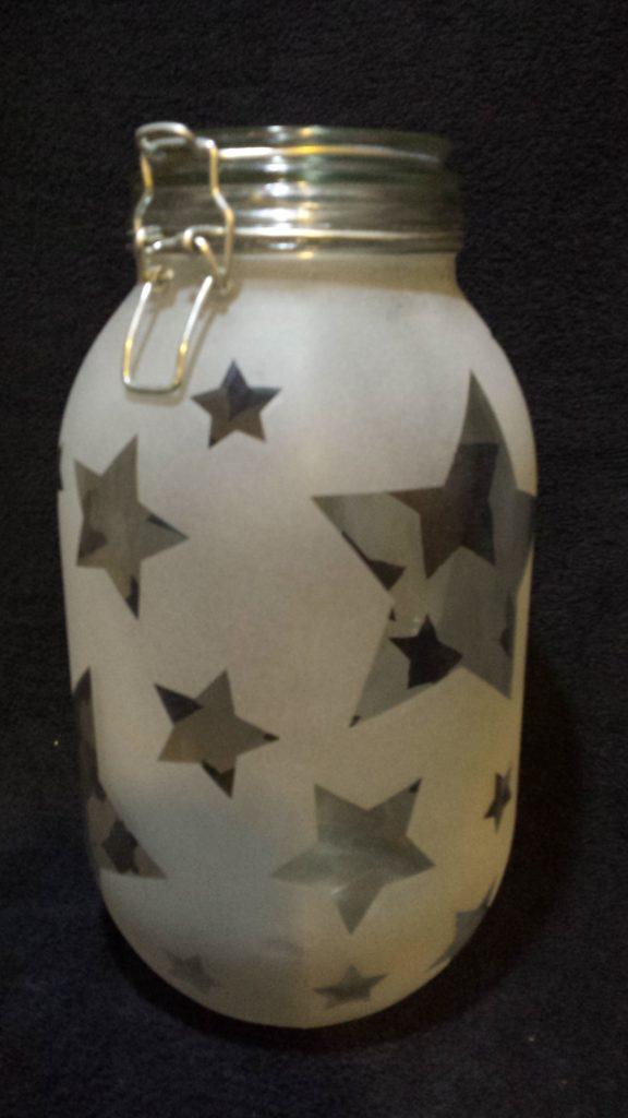 A large preserving jar with a reverse etched star pattern
