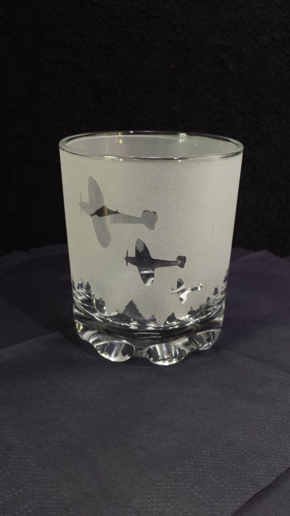 Reverse etched spitfire design of a tumbler