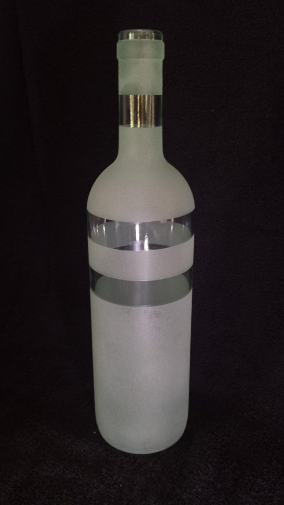 A clear glass bottle reverse etched with horizontal bands