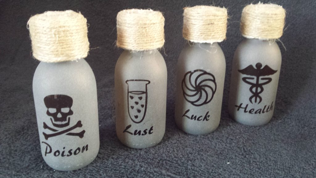 A group of potion bottles reverse etched with various designs