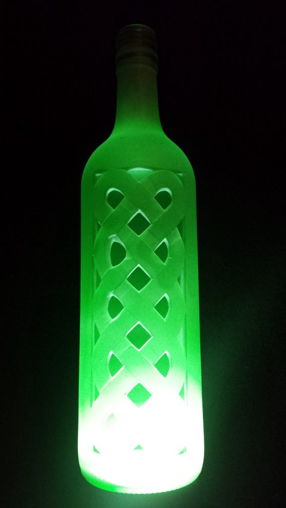 A green frosted bottle underlit with a celtic knotwork design carved through the glass
